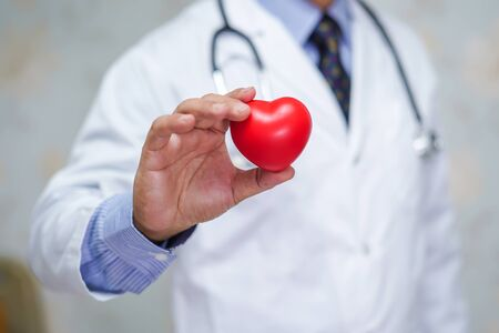 Doctor holding red heart in his hand in nursing hospital ward : healthy strong medical concept  Standard-Bild