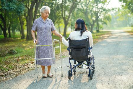 Asian senior or elderly old lady walk with walker in park and woman in wheelchair in park: healthy strong medical concept