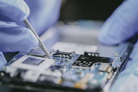 E-waste, technician repairing inside of mobile phone by soldering iron. Integrated Circuit. the concept of data, hardware, technician and technology.