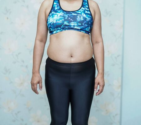 Overweight Asian woman show fat belly at office.
