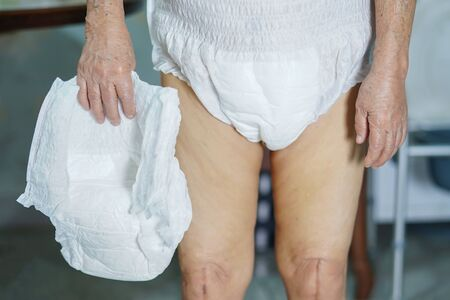 Asian senior or elderly old lady woman patient wearing incontinence diaper in nursing hospital ward : healthy strong medical concept. Stock Photo