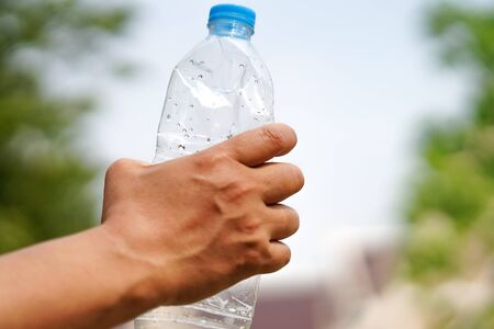Hand squeeze empty water bottle prepare throw into the trash.