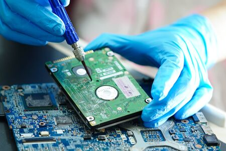 Asian Technician repairing micro circuit main board computer electronic technology : hardware, mobile phone, upgrade, cleaning concept.