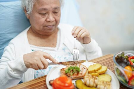 Asian senior or elderly old lady woman patient eating breakfast on bed in hospital.