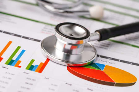 Stethoscope on charts and graphs spreadsheet paper, Finance, Account, Statistics, Investment, Analytic research data economy and Business company concept. Zdjęcie Seryjne