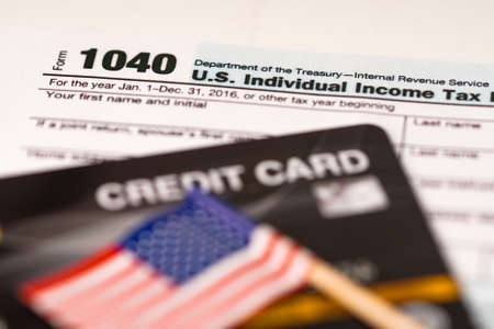 Tax Return form 1040 with credit card and USA flag : U.S. Individual Income.