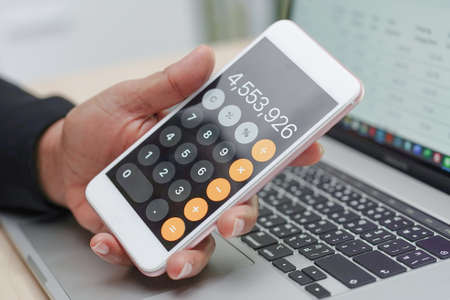 Asian accountant working, calculate and analyzing report project accounting with notebook, calculator in mobile phone in modern office : finance and business concept.