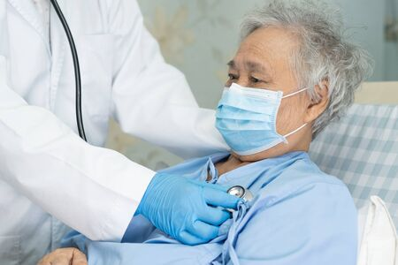 Asian senior or elderly old lady woman patient wearing a face mask in hospital for protect infection and kill Novel Coronavirus (2019-nCoV) Covid-19 virus.