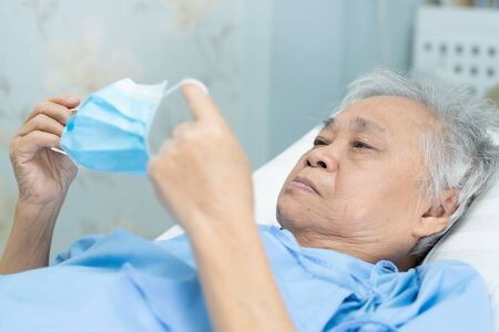 Asian senior or elderly old lady woman patient wearing a face mask in hospital for protect infection and kill Novel Coronavirus (2019-nCoV) Covid-19 virus. Standard-Bild - 143869622