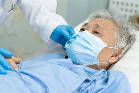Doctor help Asian senior or elderly old lady woman patient wearing a face mask in hospital for protect safety infection and kill Novel Coronavirus (2019-nCoV) Covid-19 virus. Standard-Bild - 143871194