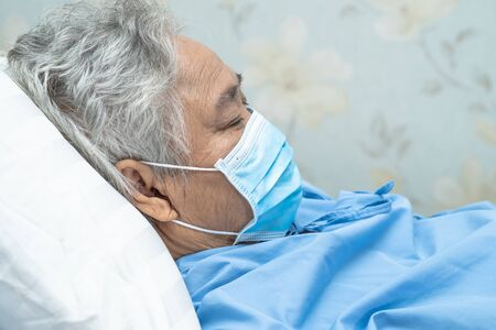 Asian senior or elderly old lady woman patient wearing a face mask in hospital for protect safety infection and kill Novel Coronavirus (2019-nCoV) Covid-19 virus. Standard-Bild - 143871072