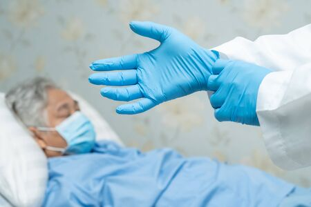 Asian senior or elderly old lady woman patient wearing a face mask with doctor in hospital for protect safety infection and kill Novel Coronavirus (2019-nCoV) Covid-19 virus. Standard-Bild - 143871086