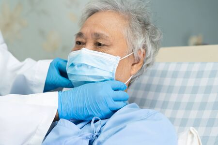 Doctor help Asian senior or elderly old lady woman patient wearing a face mask in hospital for protect safety infection and kill Novel Coronavirus (2019-nCoV) Covid-19 virus. Standard-Bild - 143871115