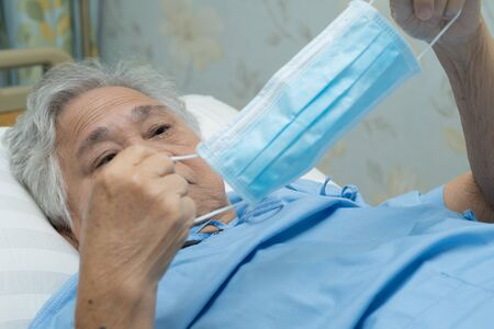 Asian senior or elderly old lady woman patient wearing a face mask in hospital for protect safety infection and kill Novel Coronavirus (2019-nCoV) Covid-19 virus. Standard-Bild - 143871560