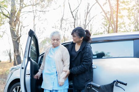 Help and support asian senior or elderly old lady woman patient sitting on wheelchair prepare get to her car : healthy strong medical concept. Stok Fotoğraf