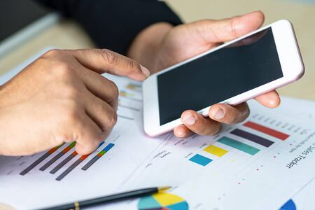 Accounting press mobile phone with chart graph for working project in modern office. Imagens
