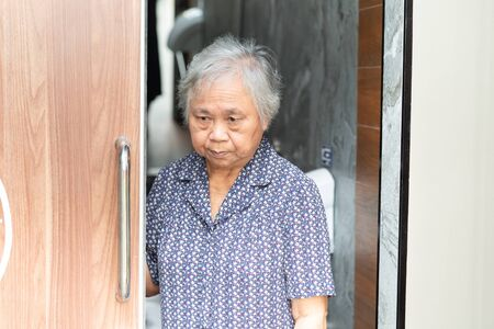 Asian senior elderly old lady woman patient open toilet bathroom by hand in nursing hospital ward : healthy strong medical concept.