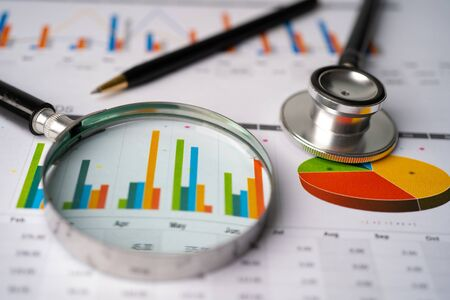 Magnifying glass, stethoscope and pen on charts graphs paper. Financial development, Banking Account, Statistics, Investment Analytic research data economy, Stock exchange trading, Business office company meeting concept. Stok Fotoğraf