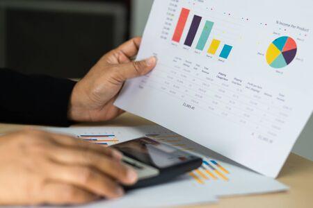 Asiatischer Buchhalter, der Finanzberichte bearbeitet und analysiert, Projektbuchhaltung mit Diagrammgrafik und Taschenrechner im modernen Büro: Finanz- und Geschäftskonzept.