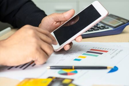 Asian accountant working and analyzing financial reports project accounting with mobile phone, chart graph and calculator in modern office,finance and business concept. Banco de Imagens