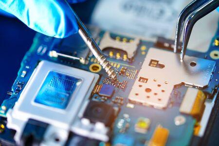 Técnico asiático que repara la placa principal del microcircuito de la tecnología electrónica del teléfono inteligente: computadora, hardware, teléfono móvil, actualización, concepto de limpieza.
