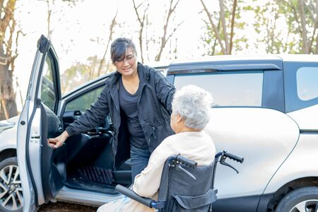 Help and support asian senior or elderly old lady woman patient sitting on wheelchair prepare get to her car, healthy strong medical concept.