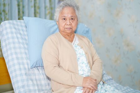Asian senior or elderly old lady woman patient smile bright face while sitting on bed in nursing hospital ward, healthy strong medical concept.