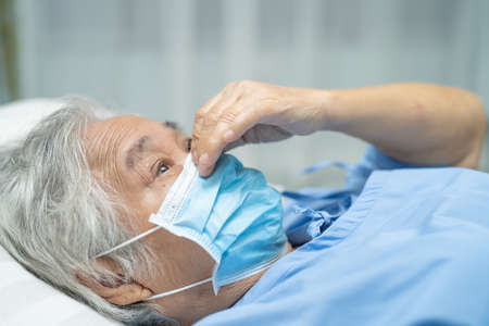 Asian senior or elderly old lady woman patient wearing a face mask in hospital for protect safety infection and kill Novel Coronavirus Covid-19 virus.