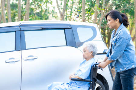 Help and support asian senior or elderly old lady woman patient sitting on wheelchair prepare get to her car, healthy strong medical concept. Foto de archivo