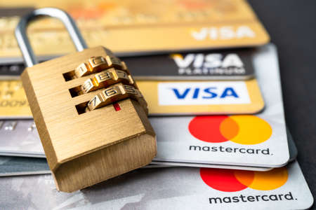 Bangkok, Thailand - July 1, 2020 Golden security digital password lock key on visa master card background.