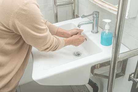 Asian washing hand by liquid soap and clean water for protect safety infection and kill Novel Coronavirus Covid-19 virus, bacteria and germs.