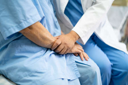 Touching hands Asian senior or elderly old lady woman patient with love, care, helping, encourage and empathy at nursing hospital ward : healthy strong medical concept Standard-Bild