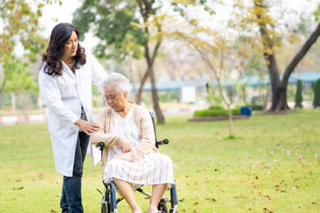 Doctor help and care Asian senior or elderly old lady woman patient sitting on wheelchair at park in nursing hospital ward : healthy strong medical concept