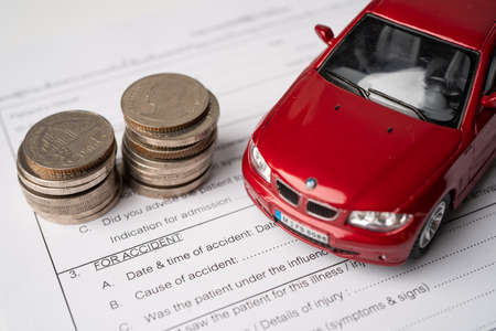 BANGKOK, THAILAND - JULY 1, 2020 Car and coins on Insurance claim accident car form background, Car loan, Finance, saving money, insurance and leasing time concepts.