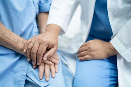 Touching hands Asian senior or elderly old lady woman patient with love, care, encourage and empathy at nursing hospital ward, healthy strong medical concept