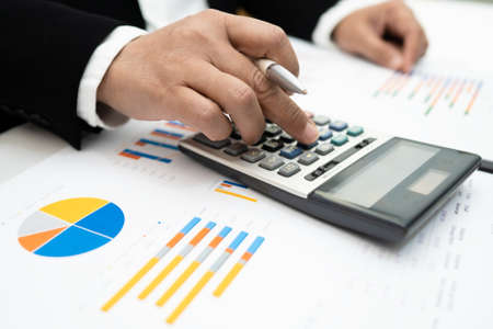 Asian accountant working and analyzing financial reports project accounting with chart graph and calculator in modern office,finance and business concept. Standard-Bild