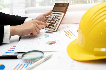 Architect or engineer working project accounting with graph and construction helmet in office, Construction account concept. 写真素材