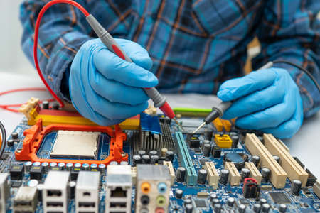 Technician repairing micro circuit main board computer electronic technology, hardware, mobile phone, upgrade, cleaning concept.