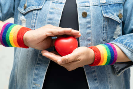 Asian lady wearing rainbow wristbands and hold red heart, symbol of LGBT pride month celebrate annual in June social of gay, lesbian, bisexual, transgender, human rights.