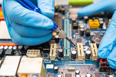 technician repairing inside of hard disk by soldering iron. Integrated Circuit. the concept of data, hardware, technician and technology. Archivio Fotografico