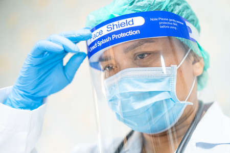 Asian doctor wearing face shield and PPE suit new normal to check patient protect safety infection Covid-19 Coronavirus outbreak at quarantine nursing hospital ward.