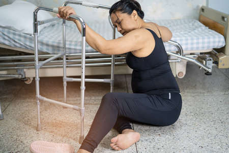 Asian middle-aged lady woman patient falling in living room because slippery surfaces Reklamní fotografie