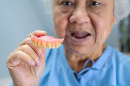 Asian senior or elderly old woman patient holding to use denture in nursing hospital ward, healthy strong medical concept Imagens