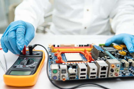 Multimeter with main board, maintenance, repairing and checking computer hardware concept.