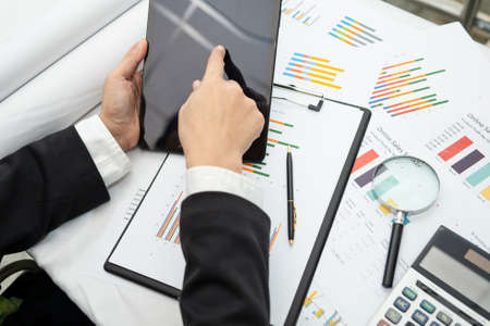Asian accountant working and analyzing financial reports project accounting with chart graph and calculator in modern office,finance and business concept. 版權商用圖片