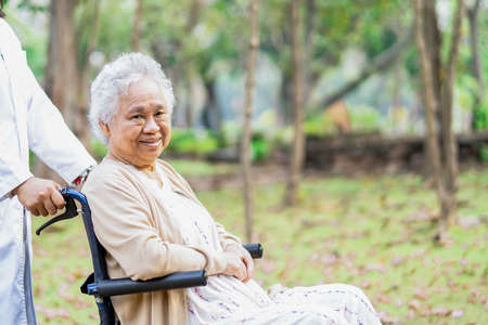Doctor help and care Asian senior or elderly old lady woman patient sitting on wheelchair at park in nursing hospital ward, healthy strong medical concept. 写真素材
