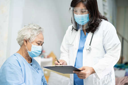 Doctor using stethoscope to checking Asian senior or elderly old lady woman patient wearing a face mask in hospital for protect infection Covid-19 Coronavirus.