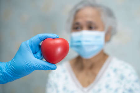 Doctor give red heart to Asian senior or elderly old lady woman patient, healthy strong medical concept