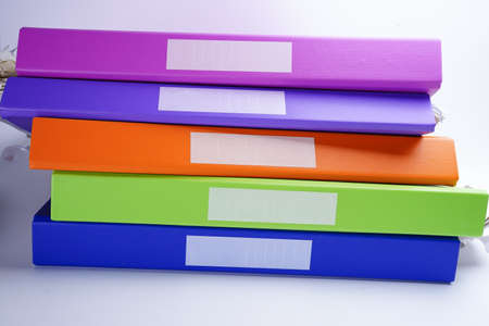 File Folder Binder stack of multi color on table in office.