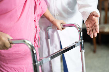 Doctor help and care Asian senior or elderly old lady woman use walker with strong health while walking in hospital.